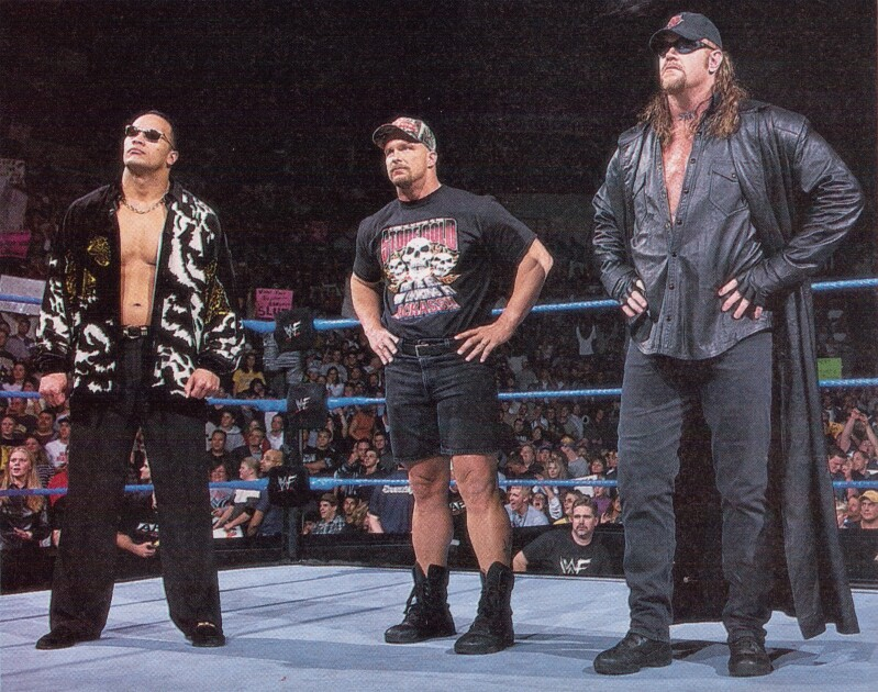 The Rock, Stone Cold Steve Austin, and The Undertaker stand in the ring during the Attitude Era of WWF