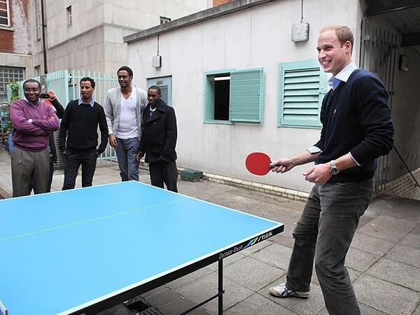 The Duke of Cambridge, Prince William, plays ping pong with the homeless