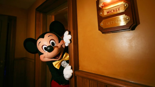 Mickey Mouse peeks out of a door