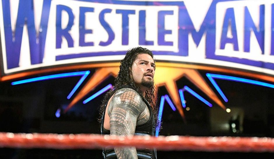 Roman Reigns poses in front of the massive Wrestlemania sign