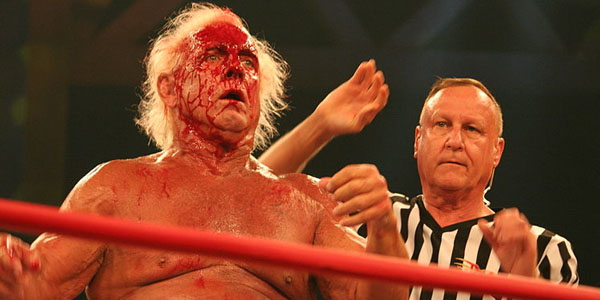 Ric Flair is a bloody mess as referee Earl Hebner looks on