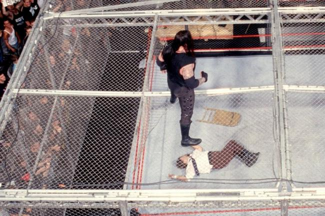 The Undertaker looks down on Mick Foley after dropping him through the ceiling of the Hell in a Cell