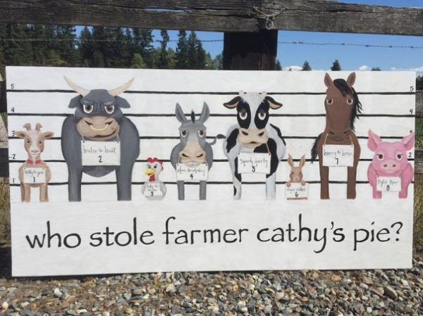 "A poster for a corn maze that reads, ""Who stole farmer cathy's pie?"""
